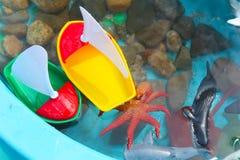 Crian?as que jogam com os brinquedos da vida dos barcos e da criatura/oceano do mar em uma tabela de ?gua imagem de stock royalty free
