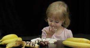 A crian?a come a banana, a morango com chocolate derretido e o chantiliy vídeos de arquivo