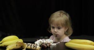 A crian?a come a banana, a morango com chocolate derretido e o chantiliy video estoque