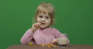 A crian?a come bolinhos Uma menina est? comendo as cookies que sentam-se na tabela foto de stock