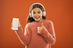 A crian?a da menina escuta fones de ouvido e smartphone modernos da m?sica Obtenha a assinatura da fam?lia da m?sica Acesso a mil foto de stock royalty free
