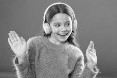 Crian?a da menina para escutar fones de ouvido sem fio modernos da m?sica Escute livre Obtenha a assinatura da conta da m?sica Ac foto de stock royalty free