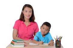 Crian?a de ajuda do professor novo com escrita da li??o isolada no fundo branco imagens de stock royalty free