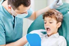 A crian?a e o dentista do menino est?o verificando os dentes no espelho fotos de stock royalty free