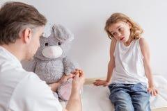Crian?a e pediatra doentes tristes no escrit?rio do doutor fotos de stock