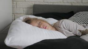 Crian?a feliz da menina que acorda esticando os bra?os na cama na manh? Sa?de, beleza e conceito da inf?ncia video estoque