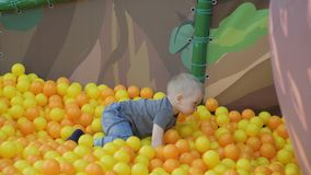 Crian?a feliz, menino da crian?a que joga, tendo o divertimento no campo de jogos com as bolas pl?sticas coloridas na associa??o  video estoque