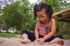 Crian?a feliz que joga com areia, fam?lia asi?tica engra?ada em um parque fotos de stock