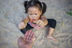 Crian?a feliz que joga com areia, fam?lia asi?tica engra?ada em um parque foto de stock royalty free