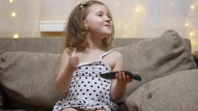 A crian?a gerencie sobre a tev? usando o telecontrole Televis?o de observa??o do beb? filme
