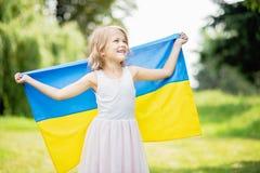 A crian?a leva a vibra??o bandeira azul e amarela de Ucr?nia no campo Dia da Independ?ncia do ` s de Ucr?nia Dia de bandeira Dia  fotografia de stock royalty free