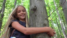 Crian?a na floresta, crian?a que joga na natureza, menina na aventura exterior atr?s de uma ?rvore