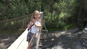 Crian?a na ponte nas montanhas, crian?a que caminha na natureza, menina que olha um rio, c?rrego