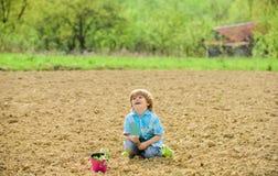 crian?a pequena que planta uma flor Dia de terra Vida nova Explora??o agr?cola do ver?o Jardineiro feliz da crian?a Trabalhador b fotos de stock royalty free