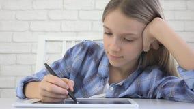 Crian?a que estuda na tabuleta, menina que escreve na turma escolar, aprendendo fazendo trabalhos de casa imagens de stock