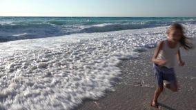 Crian?a que joga na praia, ondas de observa??o do mar, menina que corre no litoral no ver?o filme