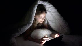 Crian?a que joga a tabuleta na noite escura, Internet da consulta??o da menina na cama, n?o dormindo video estoque