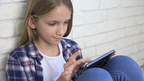 Crian?a que joga a tabuleta, crian?a Smartphone, mensagens da leitura da menina que consultam o Internet video estoque