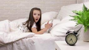 A crian?a que pequena bonito a menina se encontra na cama usa a tabuleta digital video estoque