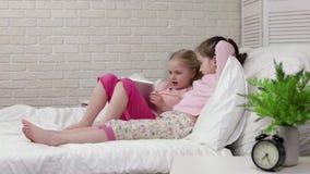 A crian?a que pequena bonito a menina se encontra na cama usa a tabuleta digital