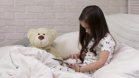 A crian?a que pequena bonito a menina se encontra na cama usa a tabuleta digital vídeos de arquivo