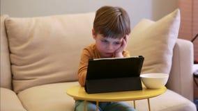 Crian?a que usa o PC da tabuleta na cama em casa O menino bonito no sof? est? olhando desenhos animados, est? jogando jogos e est video estoque