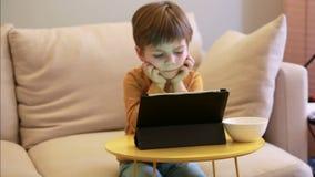 Crian?a que usa o PC da tabuleta na cama em casa O menino bonito no sof? est? olhando desenhos animados, est? jogando jogos e est filme