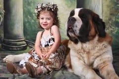Criança adorável e seu cão de filhote de cachorro de Bernard de Saint Imagem de Stock