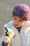 Criança adorável que olha flores Foto de Stock Royalty Free