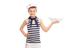 Criança alegre em um equipamento do marinheiro que guarda um barco de papel Fotos de Stock