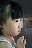 A criança asiática pequena triste olha na janela Imagens de Stock