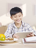 Criança asiática que usa o tablet pc Imagens de Stock