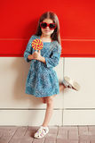 Criança bonita da menina com o pirulito que veste um vestido e óculos de sol do leopardo sobre o vermelho Foto de Stock Royalty Free