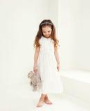 A criança bonito bonita da menina com urso de peluche brinca em casa Imagem de Stock