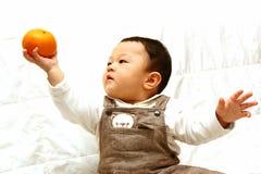 Criança bonito com laranja Fotos de Stock