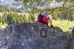 Criança bonito que descansa na grande rocha perto do lago Oeschinensee em Bernese Oberland, Suíça Fotografia de Stock Royalty Free