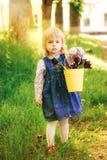 A criança com a cesta amarela da tulipa roxa floresce na mola excede Imagem de Stock
