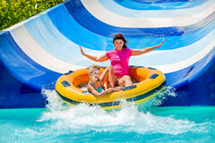 Criança com a matriz na corrediça de água no aquapark Imagens de Stock