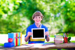 Criança com o tablet pc na jarda de escola Foto de Stock Royalty Free