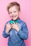 Criança considerável nova que sorri com o laço azul da camisa e de borboleta Retrato do estúdio sobre o fundo cor-de-rosa Fotos de Stock Royalty Free