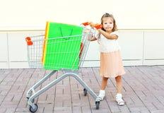 Criança da menina e carro felizes do trole com os sacos de compras coloridos na cidade Imagens de Stock