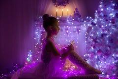 Criança da menina, luzes da árvore de Natal, criança na noite do feriado Foto de Stock