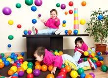Criança da moça que tem o divertimento que joga com as bolas plásticas coloridas Imagem de Stock Royalty Free
