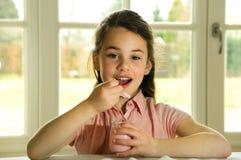 Criança de cabelo de Brown que come o yogurt Fotos de Stock Royalty Free
