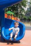 Criança de quatro anos que monta uma montanha russa no campo de jogos Fotos de Stock Royalty Free