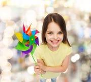 Criança de sorriso com o brinquedo colorido do moinho de vento Imagens de Stock Royalty Free