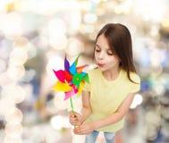Criança de sorriso com o brinquedo colorido do moinho de vento Fotos de Stock