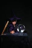 Criança do feiticeiro com esfera de cristal e equipe de funcionários Imagem de Stock Royalty Free