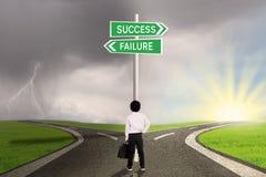 Criança do negócio que olha o sinal do sucesso ou da falha Fotografia de Stock Royalty Free