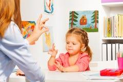 Criança em idade pré-escolar que joga o jogo da mão com professor Imagens de Stock